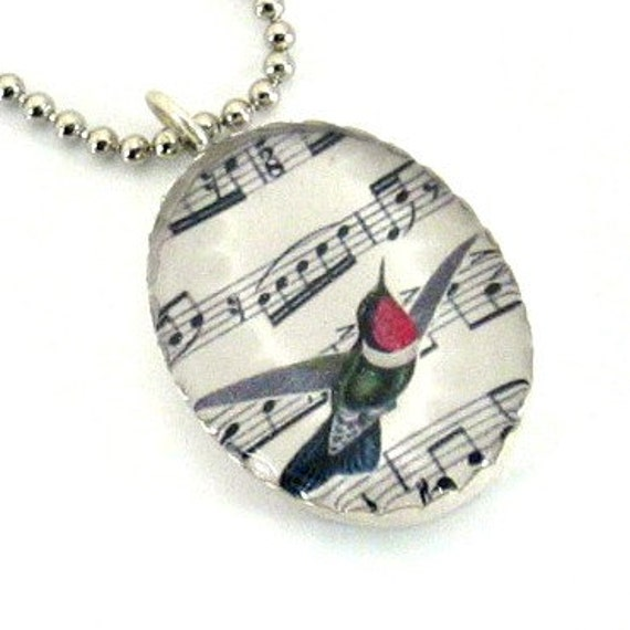 Antique hummingbird drawing with a background of the Rites of Spring's music score pendant