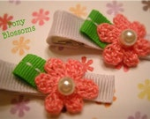 Dainty pink crochet flower clips adorned with green grosgrain petals and glass bead centers.