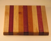 "Trivit cutting board/chopping block made of many different woods.8 x 8.5"". maple, purpleheart, ash, cherry and purpleheart center"