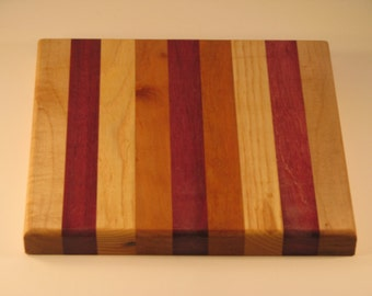 """Trivit cutting board/chopping block made of many different woods.8 x 8.5"""". maple, purpleheart, ash, cherry and purpleheart center"""
