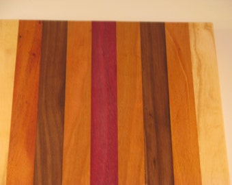 """cutting board/chopping block made of many different woods.10 x 8.5"""" with ash, mahogany, walnut, cherry and purpleheart center"""