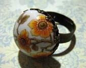 porcelain ring with vintage floral decals set in an antique brass filigree adjuststable ring