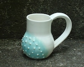 puffy cloud of greenish blue on white mug