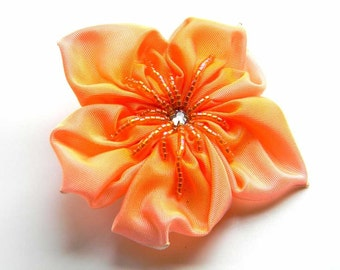 flower brooch in poranj pink fading into orange ribbon flower with beaded centre