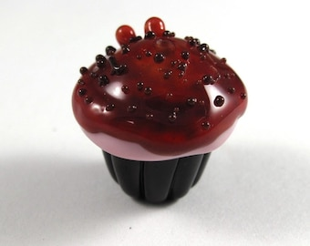 Tasty Handmade Chocolate Cupcake with Pink Frosting and Cherry Glaze and Chocolate Sprinkles with Two Cherries on Top