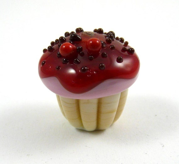 Tasty Handmade Vanilla Cupcake with Pink Frosting and Cherry Glaze and Chocolate Sprinkles with Two Cherries on Top
