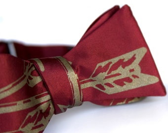 "Arrows bow tie, freestyle. Burgundy, earthy marsala red. Silkscreened necktie, antique brass print. ""Quiver."""