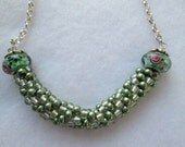 Women's hand crafted light green and clear kumihimo beaded necklace with lamp work bead accent and nickel free silver chain