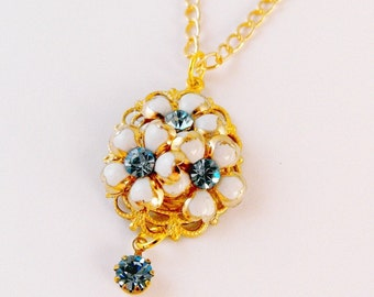 Raised Stacked White Flowers with Blue Rhinestone atop Brass Gold Plated Setting Dangle Necklace