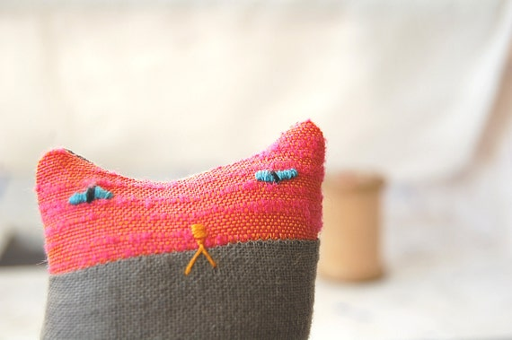 A small ornamental textile cat creature called Herb