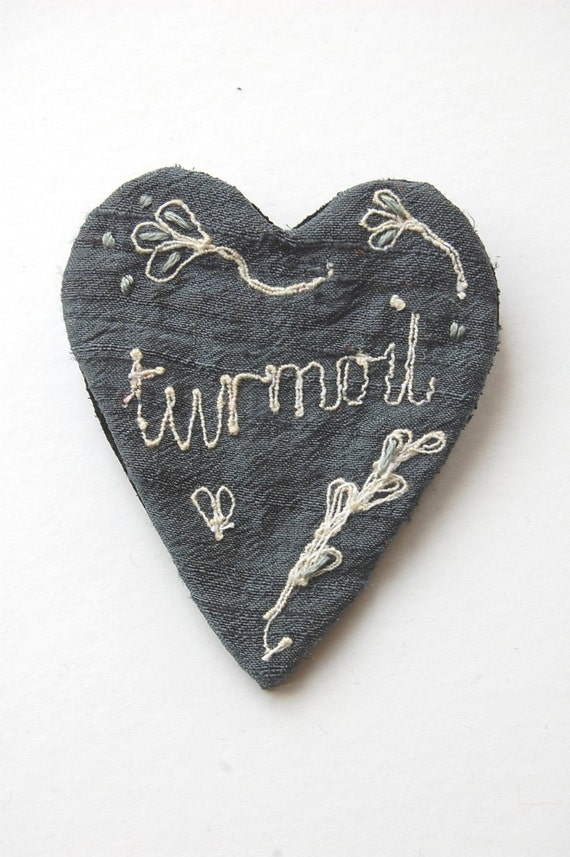Brooch embroidered silk with the word 'turmoil'
