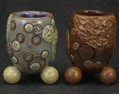 group of two olive, brown, and rust shot glasses with textured molecular motif