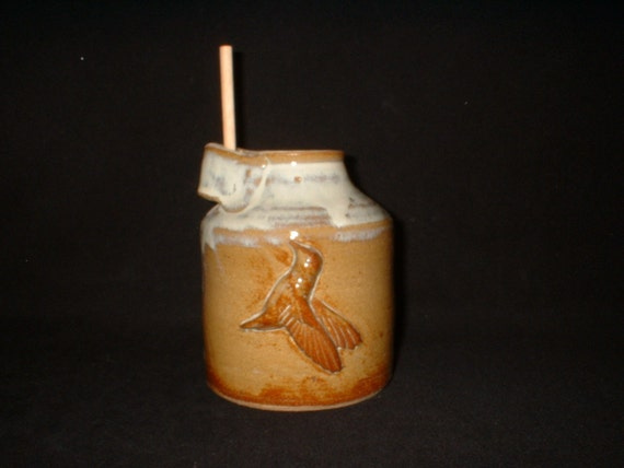 bird bottle in gold and white with hummingbird