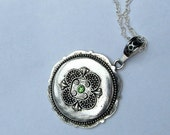 Ornamental disc necklace with green glass center