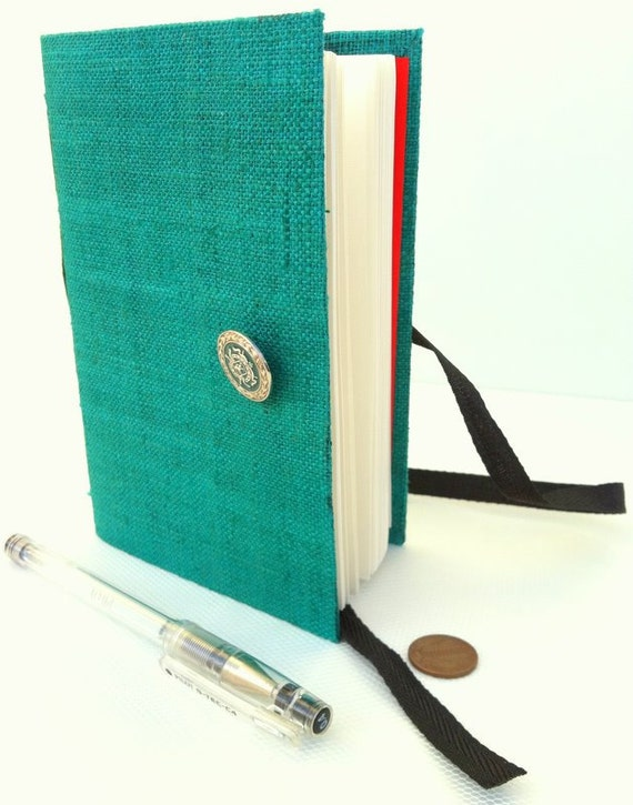 Handmade journal / notebook made with raw turquoise-green silk and opens with a matching silver green button and a dark green cotton ribbon