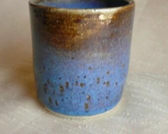 little multi-colored rustic ceramic cup