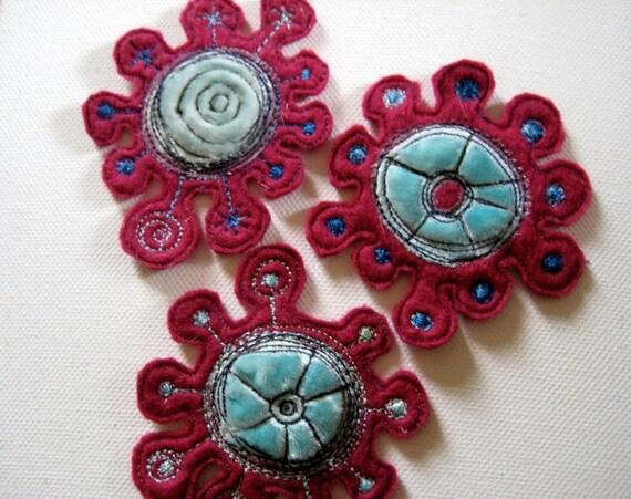 three embroidered felt shapes