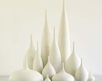 Grand Collection of 12 modern white ceramic vases in matte glaze by sara paloma. white pottery and ceramics bud vase