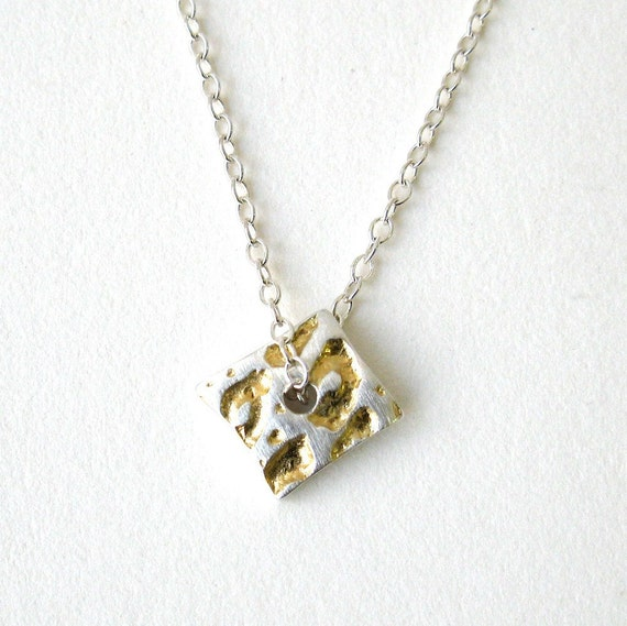 Silver leopard print pendant with gold detail.
