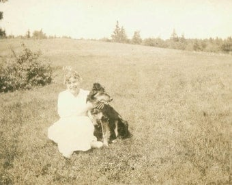 vintage photo Lady sits in field with her beautiful dog