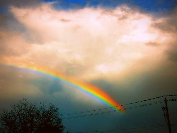Hope in the Sky: fine art photograph print of bright and colorful rainbow against dark blue sky with clouds and sunlight