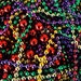 Mardi Gras Beads: a colorful fine art photograph print with red, green, purple, yellow, gold, and silver beads