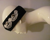 Black headband with white lace trim and metal buttons