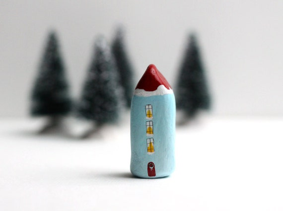 Little light blue Christmas clay house with red roof and snow