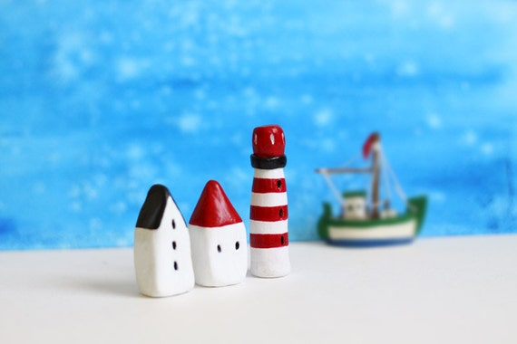 Two little clay houses and a striped lighthouse - white, black and red