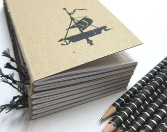 Notebook with a Sailing Ship and a Pencil