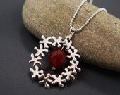 Feminine silver necklace, tiny flowers circle pendant with a red gemstone