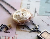cream fabric flower. bird link locket necklace. silver ox with cream color tones