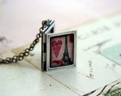 eiffel tower book. locket necklace. silver ox with pink, red, and silver color tones