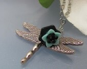 The quiet pond. A silver dragonfly and flower garden necklace