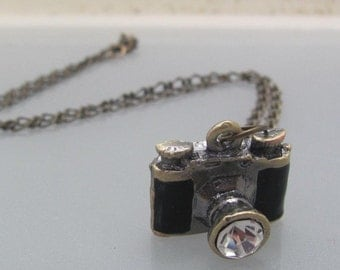 I need a camera to my eye.  Brass and black enameled camera photography necklace.