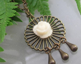 A brass and creamy rose with tiny brass rain drops necklace.