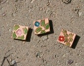 Set of three leather floral magnets, pink, blue, and red
