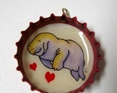 Upcycled Bottle cap necklace featuring a sweet manatee