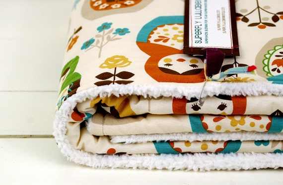 baby blanket, matryoshka or nesting dolls in autumnal tones, parent-friendly.