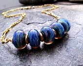 Mystique - blue swirl lampwork necklace in gold