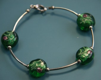 Unique one-of-a-kind bracelet of silvercolor metal with 4 handpainted rosedecorated green glass beads