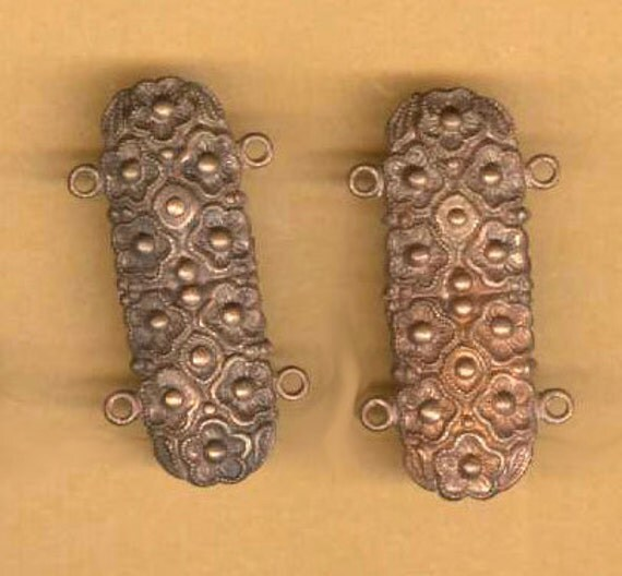 pair of fancy brass connectors, two loops on each side
