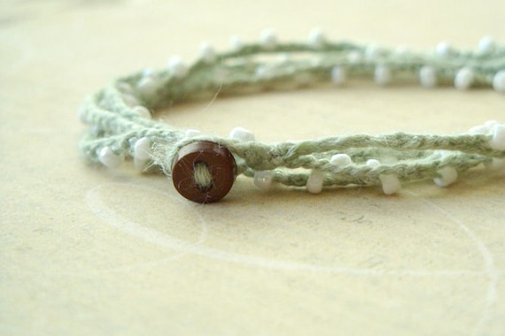 Sage green crochet wrap bracelet with pearly white seed beads and a brown button closure