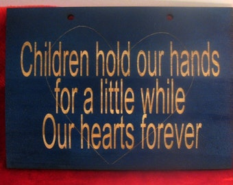 Wooden sign Children hold our hands for a little while Our hearts forever