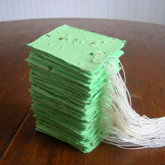 Green tags made of handmade plantable paper embedded with perennial flower seeds