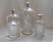 vintage etched glass clear bottles with original cork stoppers, set of three, varying sizes.