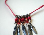 Feather charms on a red suede cord