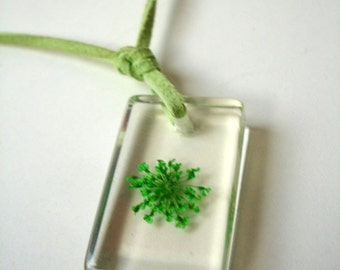 Resin pendant with lime green flower and suede cord