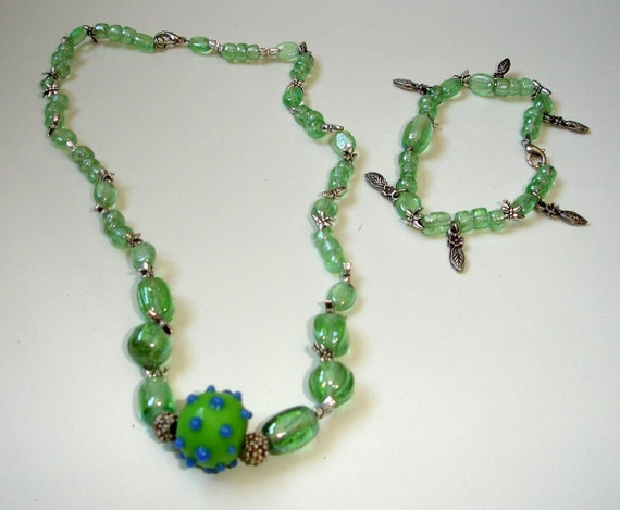 Green glass, dragonflies and feathers