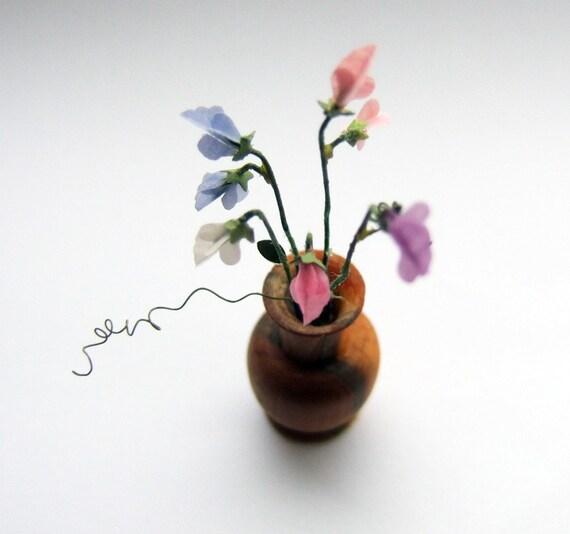Miniature sweetpeas in a turned wooden vase.